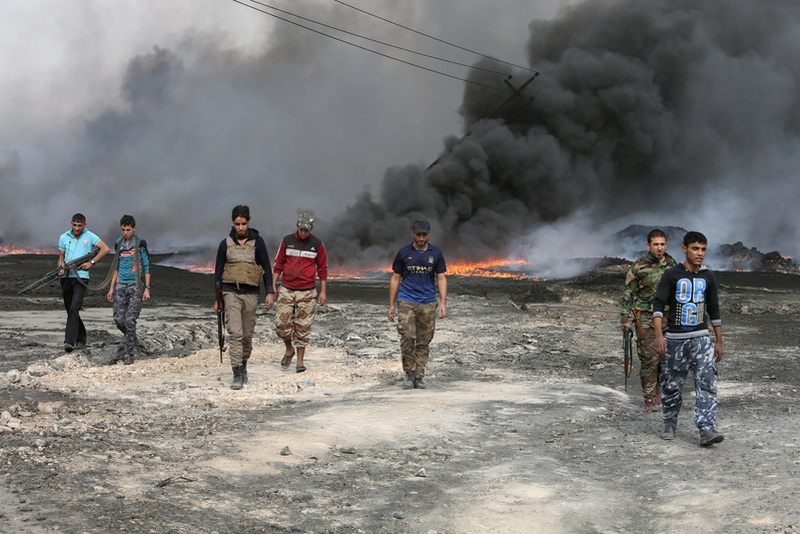 Tribal fighters walk as fire and smoke rises from oil wells, set ablaze by Islamic State militants before IS militants fled the oil-producin