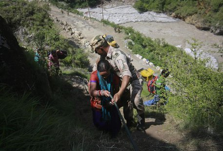 A woman is helped by a soldier to climb down a hill during a rescue operation at   Govindghat in the Himalayan state of Uttarakhand June 21, 2