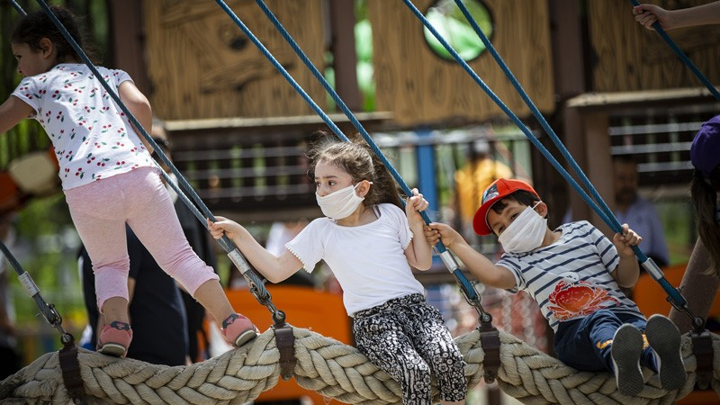 Kids wearing protective masks swing on a playground after children under 14 years across Turkey.