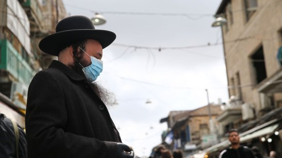 People wear face masks as a precaution against the coronavirus (COVID-19) at a tram station in Shuafat district in Jerusalem.