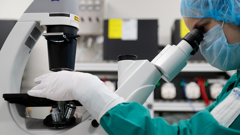 A researcher in mask, gloves and hairnet looks through a microscope.