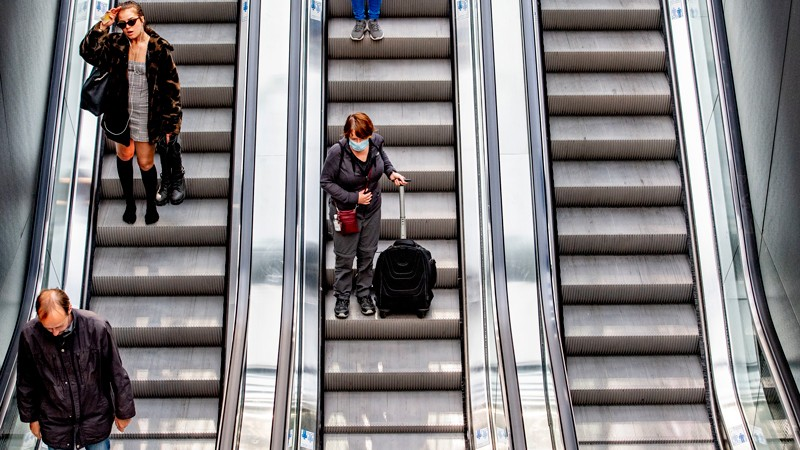 Three escalators, with people on two of them. One of the women wears a face mask.