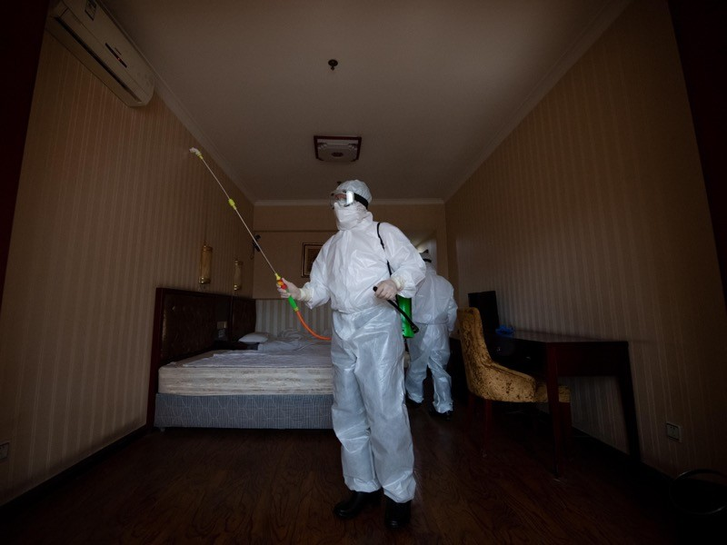 A person in full protective gear sprays a room containing a bed, desk and chair.