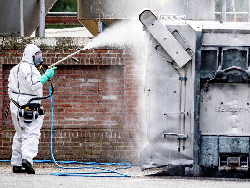 A man wearing a personal protective equipment suit (PPE) seen disinfecting the mink company.