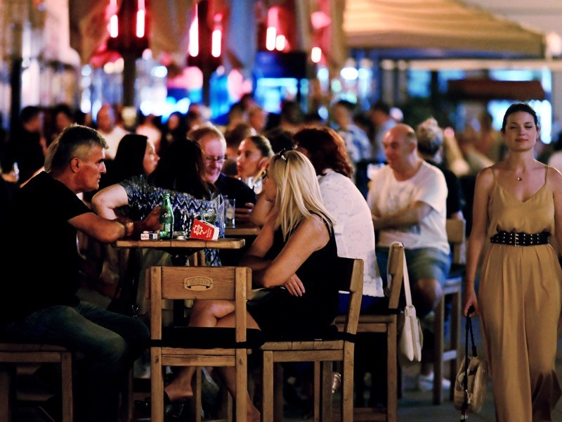 A crowd of people hanging out on the terraces of cafe bars while not wearing protective face masks, Croatia.