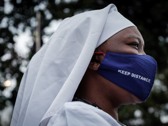 A worshipper of Legio Maria wears a protective face mask with the lettering 'Keep distance', Kenya.
