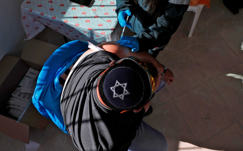 A health worker administers a dose of the Pfizer-BioNtech COVID-19 vaccine, Israel