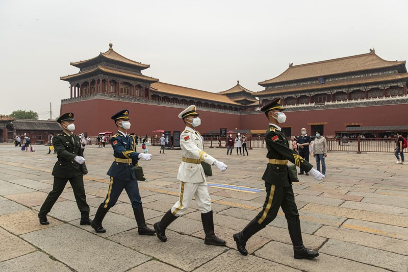 Members of the People's Liberation Army honor guards march past the Wumen Gate of the Forbidden City in Beijing