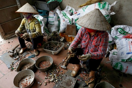 Two women in straw conical hats sit on low stools sort through bowls of electrical parts for recycling