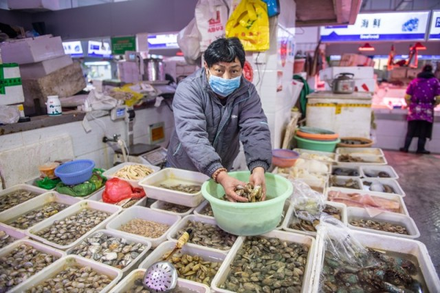 A store vendor wearing a mask handles shellfish at seafood market in China