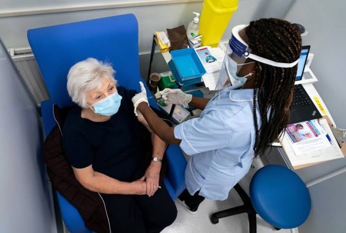 In a London hospital, a senior woman in a face mask is injected in the arm with a syringe by a hospital worker in PPE