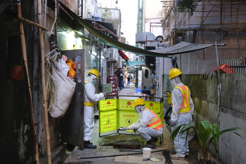 Technicians and government investigators wearing PPE take samples from a sewer in Hong Kong