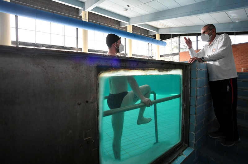 Through a window in the side of a swimming pool, a patient can be seen under water exercising on parallel bars