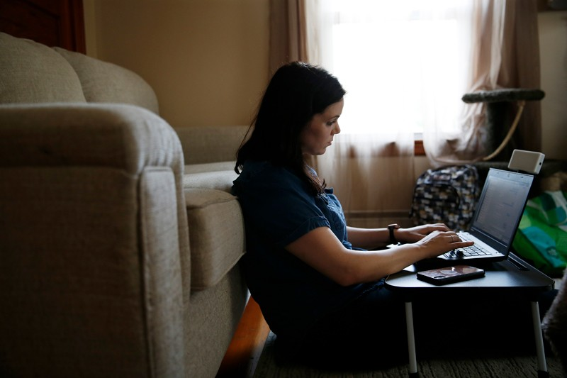 """A woman suffering from symptoms of """"long COVID"""" working on a laptop in her living room"""