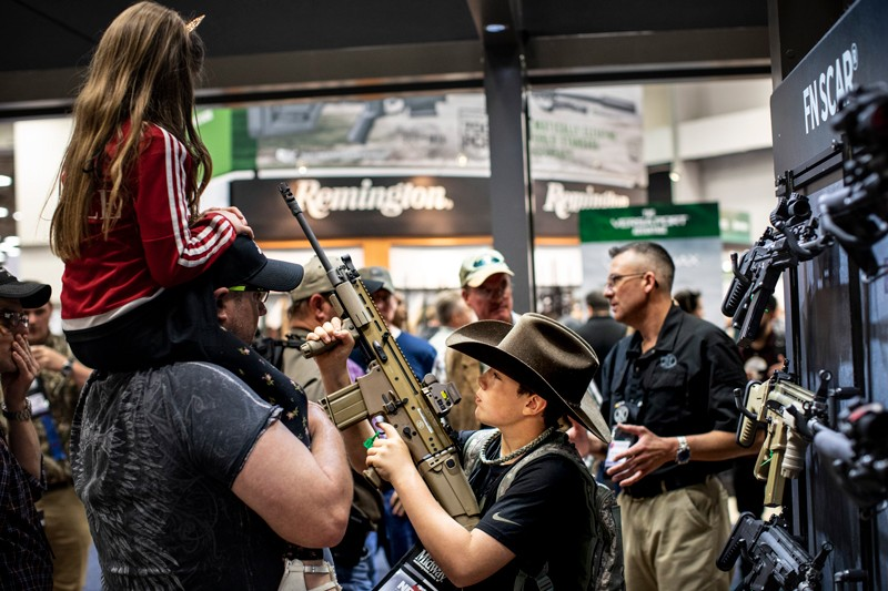 A young girls sits on a man's shoulders as a boy handles an assault rifle at a gun convention in Texas