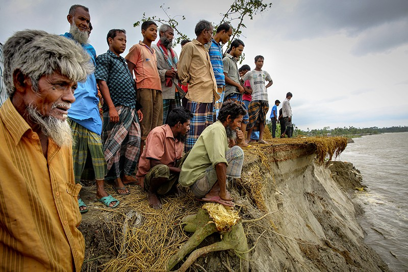 A group of villagers stands beside the Jamuna River in Bangladesh