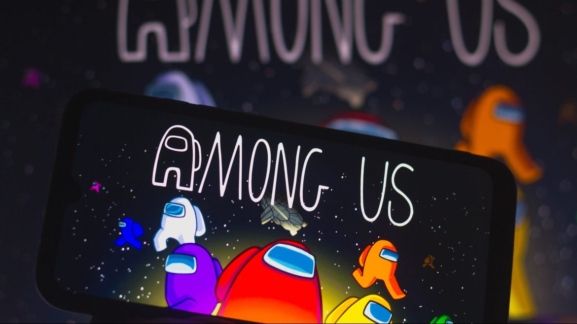 In this photo the Among Us logo is displayed on a smartphone.  Among Us is an online electronic game from the genres of group play and survival.