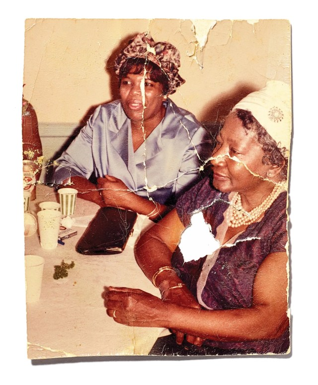 An old torn photograph of two women sitting at a table