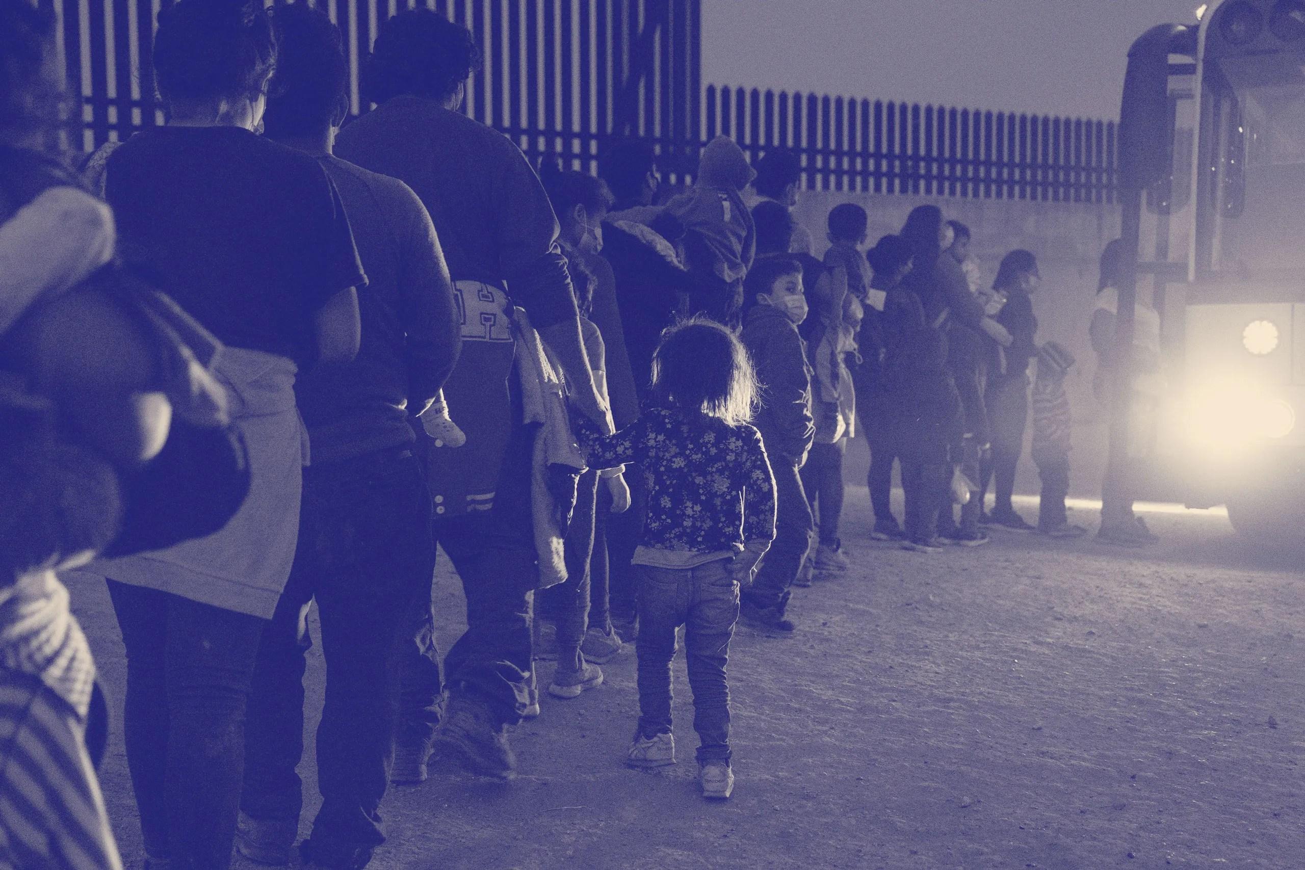 Asylumseeking migrants' families make a line to board a bus