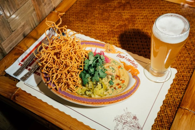Khao soi featuring a chicken leg in a creamy coconut curry topped with pickled mustard greens and crispy noodles.