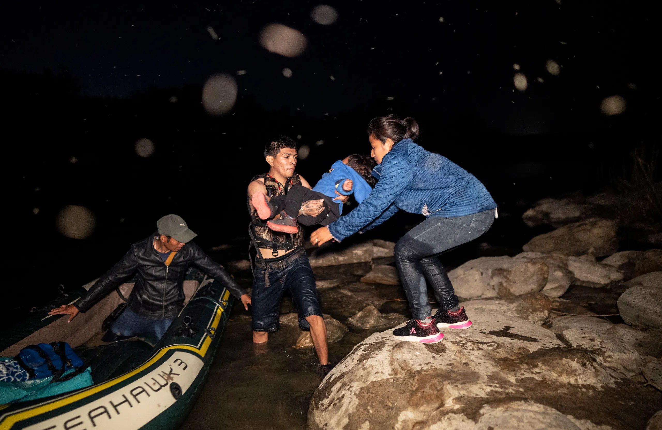A man standing in water near a boat hands a child to a woman on land.