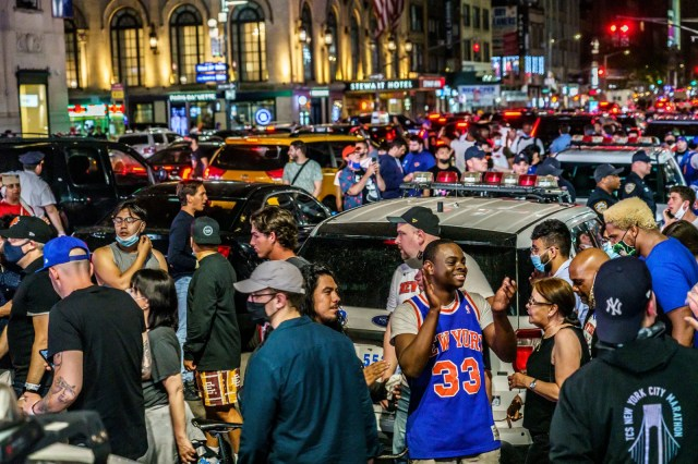 A crowd of Knicks fans celebrate outside Madison Square Garden after the win