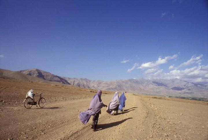 Three women walk down a dirt road towards the mountains