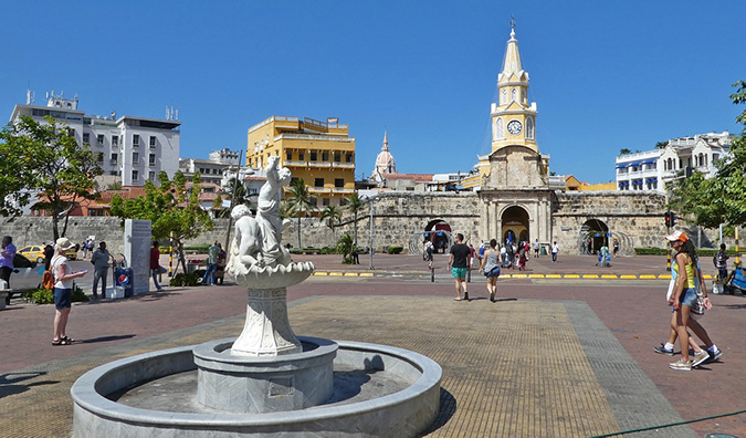 people walking around a plaza with a fountain in Cartagena, Colombia