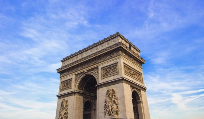 The Arc de Triomphe against a bright blue sky in Paris, France