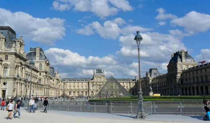 Tourists exploring the exterior of the Louvre in Paris, France
