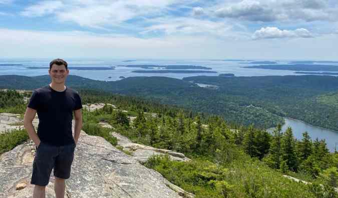 Nomadic Matt posing for a photo in Acadia National Park, Maine