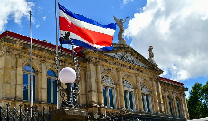 The Costa Rican flag waving in front of the historic theaer in San José, Costa Rica