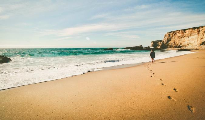 A solo female traveler walking alone on a beach