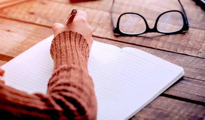 a writer writing in a fresh notebook
