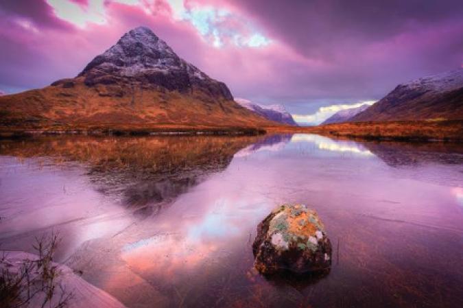 Breath-taking sunset photo over a frozen lake in Glencoe, Scotland