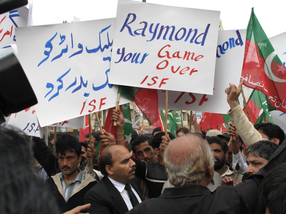"""A small but vocal crowd gathered as a Magistrate Court in Lahore decreed that Pakistani authorities may continue to hold the U.S. diplomat identified as Raymond Davis, alleged to have shot dead two Pakistani men. Protesters shouted """"Hang Davis!"""" while the U.S. Embassy cried foul.  It called his detention """"illegal"""" and said the  hearing itself violated his right to due process."""