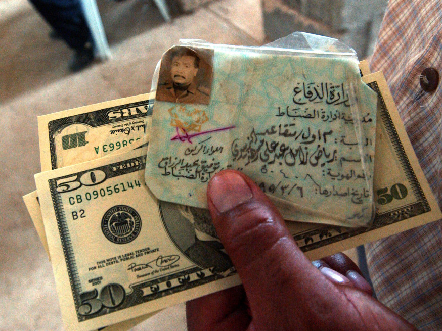 July 21, 2003: A former Iraqi Army officer holds his military I.D. and an emergency cash payment of $80.