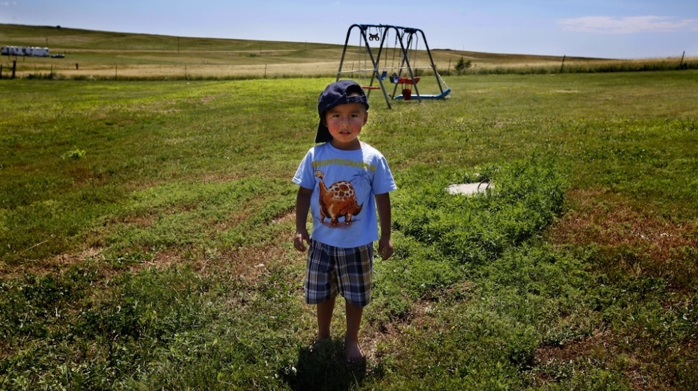 Derrin Yellow Robe, 3, stands in his great-grandparents' back yard on the Crow Creek Reservation in South Dakota. Along with his twin sister and two older sisters, he was taken off the reservation by South Dakota's Department of Social Services in July of 2009 and spent a year and a half in foster care before being returned to his family.
