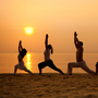 Five people on a beach stand in the warrior pose.