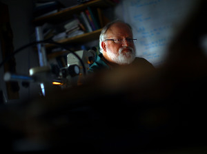 University of Arizona professor Tom Swetnam examines a tree sample at the Laboratory of Tree-Ring Research in Tucson, Ariz. Swetnam says forests are burning hotter because they are overgrown.