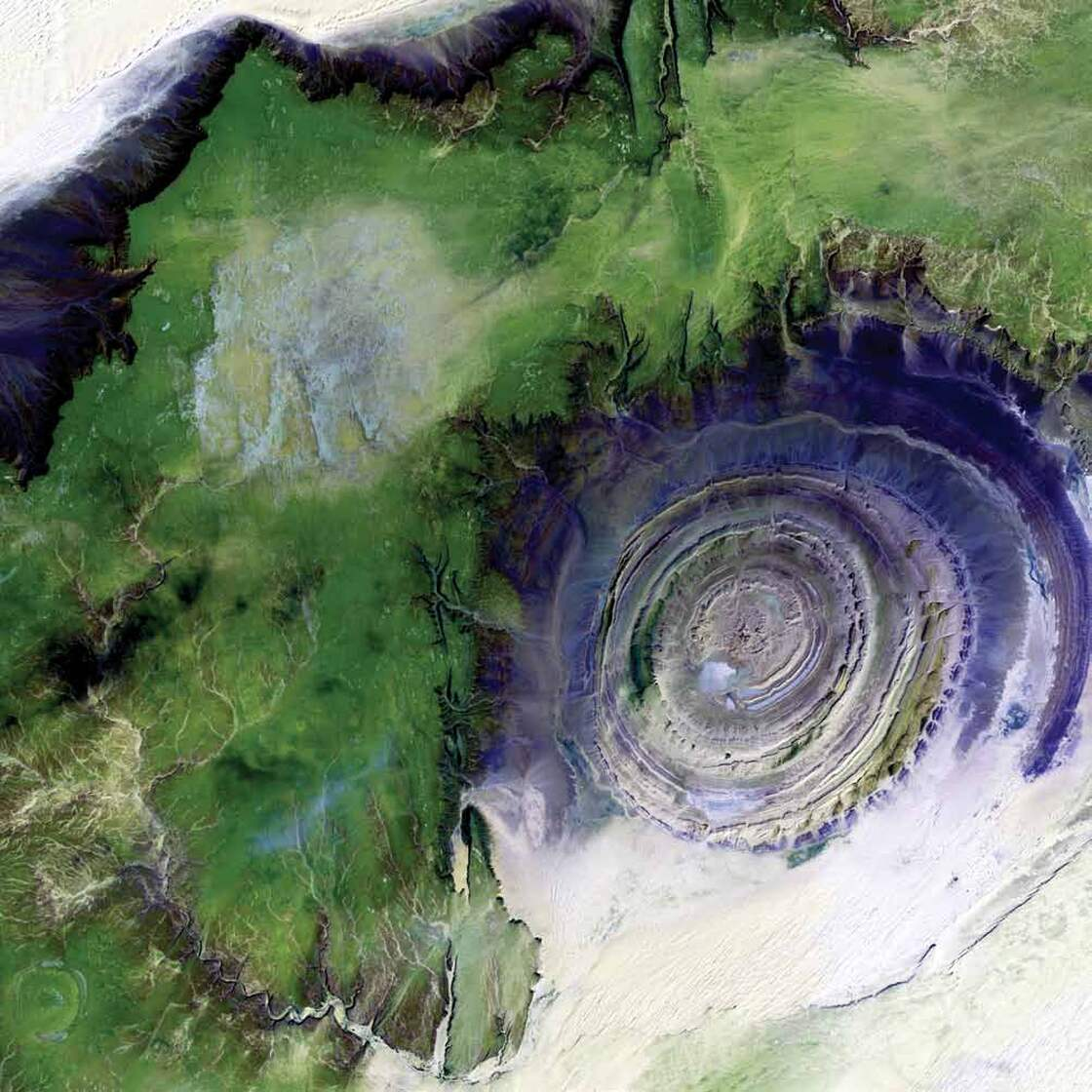 Richat Structure, Mauritania, 2001The 31-mile-wide bull's-eye in the western Sahara is a landmark for astronauts. The structure formed when a volcanic dome hardened and gradually eroded, exposing the onion-like layers of rock. Desert sands appear white and pale yellow at the corners; less sandy, rocky areas are green; and volcanic rocks are blue.