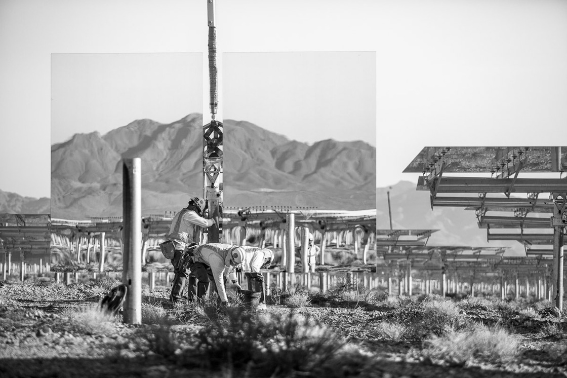 "Workers install a ""heliostat"" — or a device with a mirror that reflects the sun, or in this case the nearby mountains. Background shows assembled heliostats in ""safe"" or resting position. June 2012."