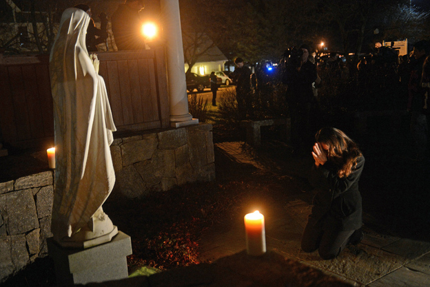 """Aline Marie prays outside St. Rose of Lima church in Newtown, Conn., on the day of the school shooting. She says being photographed made her feel """"like a zoo animal."""" The photographer says he tried hard to respect her privacy and grief."""