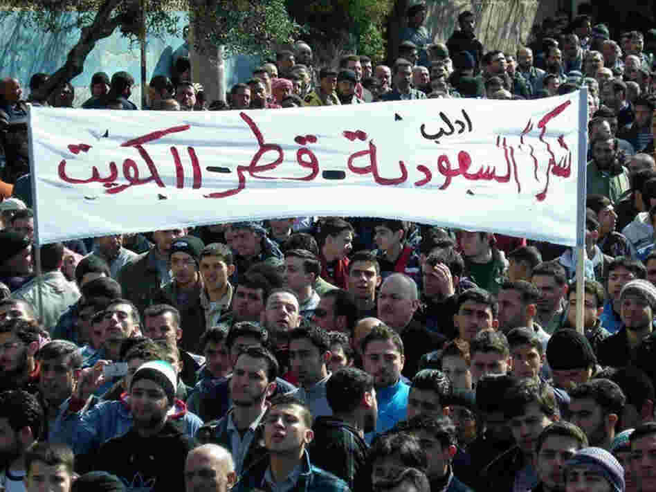 """Anti-Syrian regime protesters hold up a banner in Arabic reading, """"Thank you Saudi Arabia, Qatar and Kuwait,"""" during a demonstration in Idlib province, northern Syria, in this March 2, 2012, file photo provided by Local Coordination Committees in Syria."""