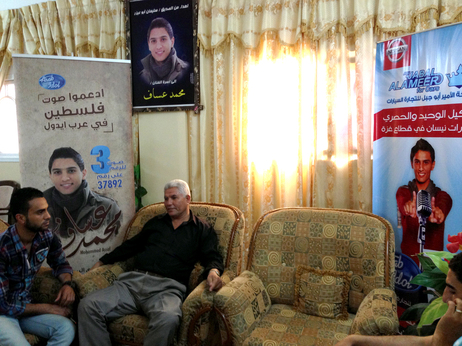 Posters of Arab Idol competitor Mohammad Assaf decorate his family's home. Both Mohammad's father, Jabar Assaf (right), and his best friend, Mohammad Abu Jabar, say a victory for the young singer from the Gaza Strip would be a win for all Palestinians.