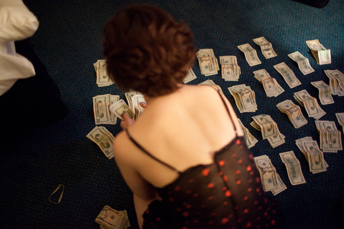 Eden counts the money she has made in the past four days. Due to the manner in which the money was obtained, she is unable to deposit it into the bank and is forced to carry it around with her.