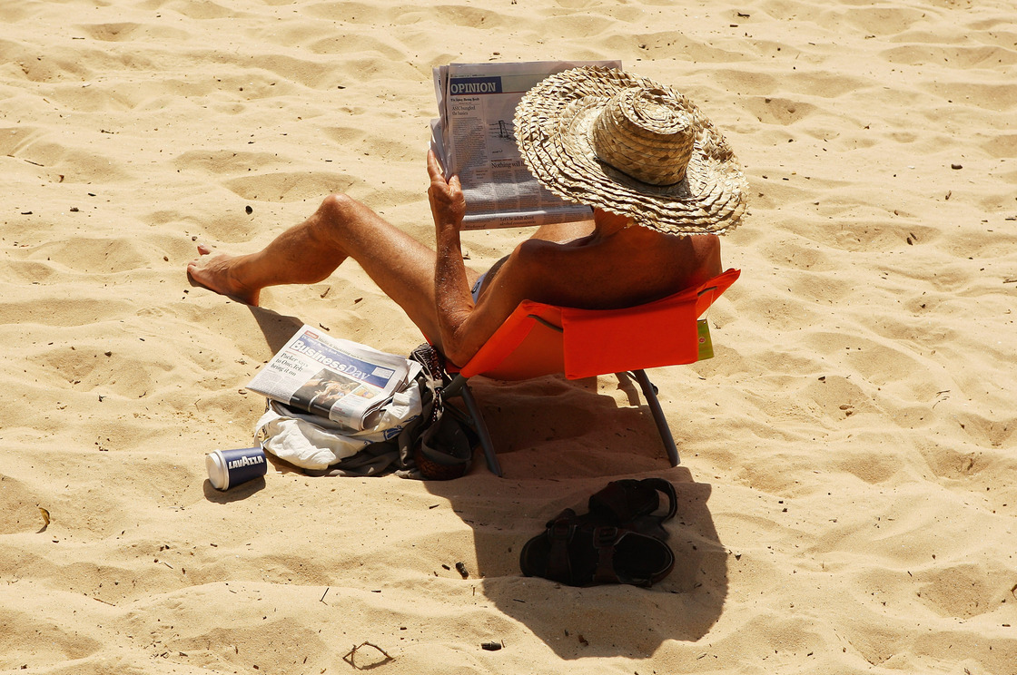 A man reads a newspaper on Balmoral beach in Sydney, Australia, in 2009.