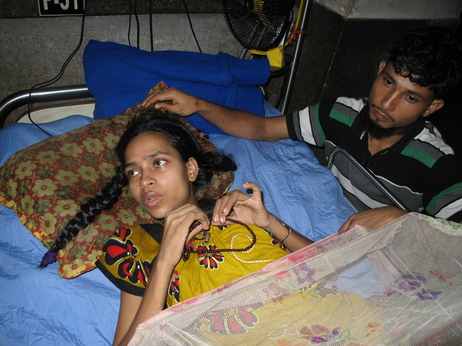 """Rebecca Khatun, a worker at Rana Plaza, lies in a hospital bed. She lost her left leg and right foot in the collapse, which also killed five members of her family. Khatun received $120 and free medical care for her loss --€"""" compensation she says won't be enough for what she's been through."""