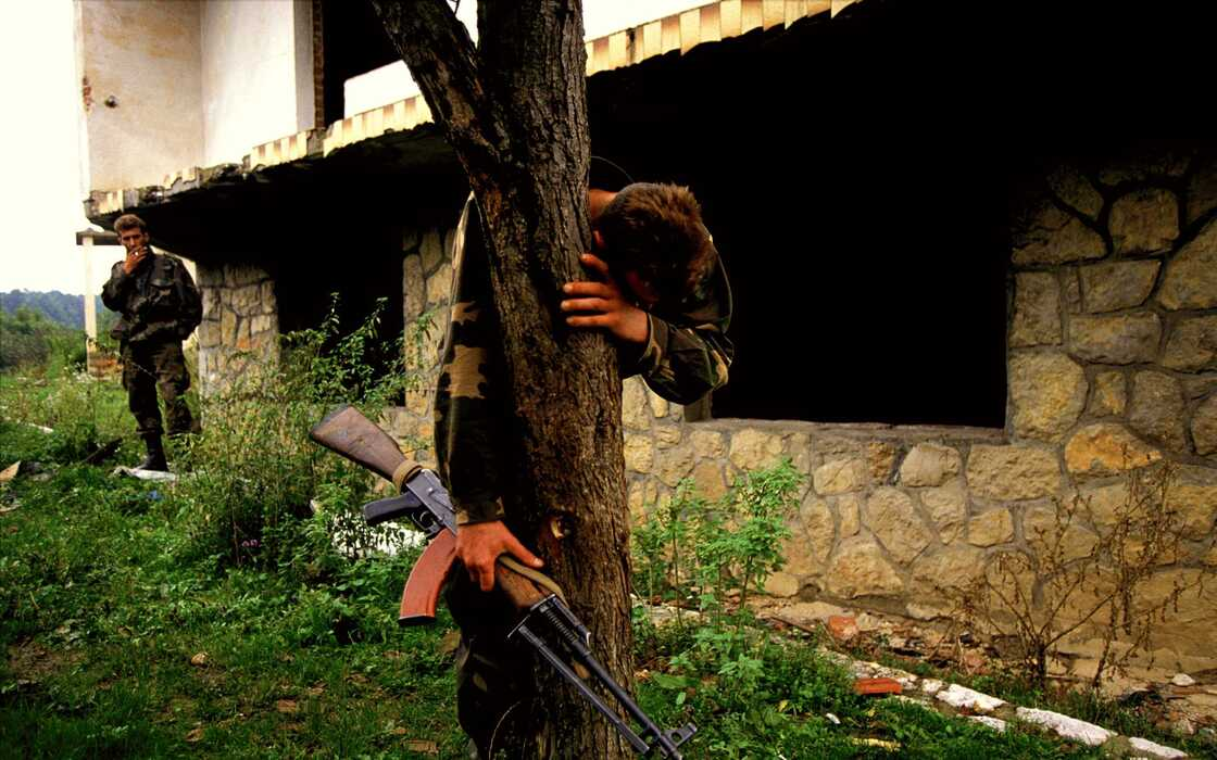 A Bosnian soldier stands on what is believed to be a mass grave outside his destroyed home. He was the sole survivor of a massacre that left 69 people dead, including his family, 1995.