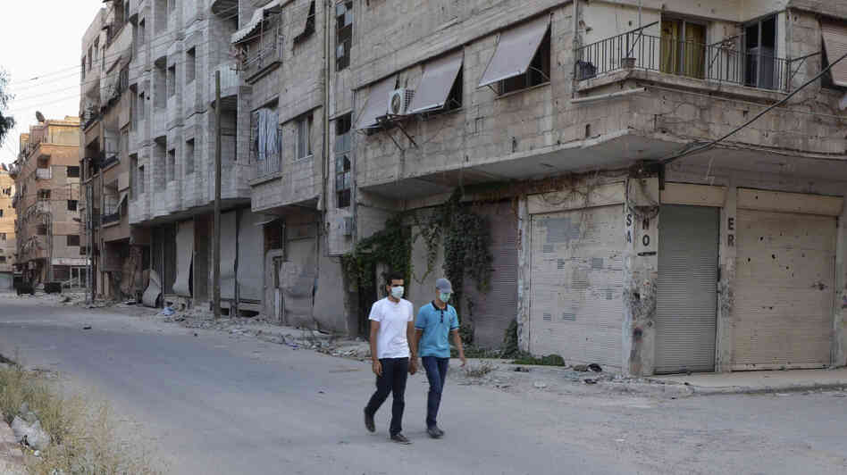 Men wearing masks walk along a deserted street that was hit by what activists said was a gas attack in the Damascus suburb of Ain Tarma on Wednesday.